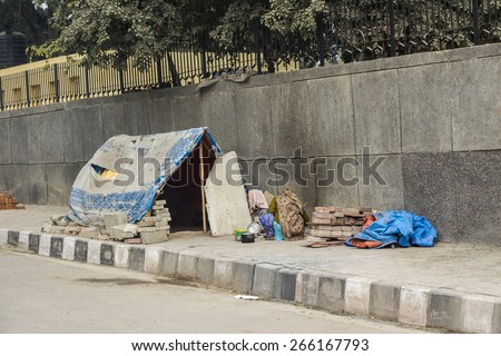temporary tent of unidentified homeless people on side of street in Delhi, India - stock photo