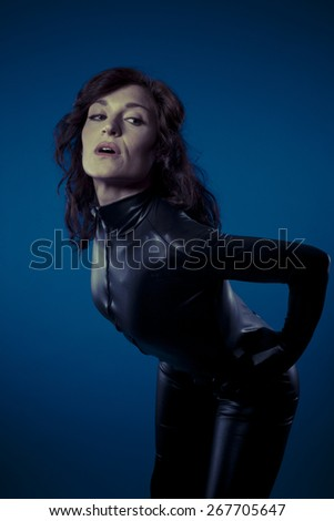 Temptation, sexy brunette in black latex bodysuit tight and wild poses - stock photo
