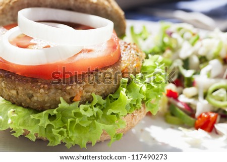 Tempting quinoa veggie burger with tomato and onion slices. - stock photo