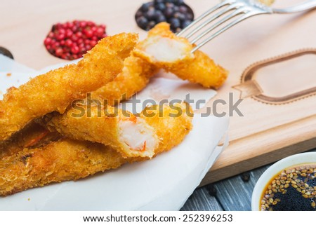 Tempura Shrimps (Deep Fried Shrimps) with sweet sauce on a wooden table with tomatoes and herbs - stock photo