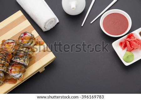 Tempura sushi roll on wooden plate ( gete ) with ginger wasabi chopsticks and sauces over black background - stock photo
