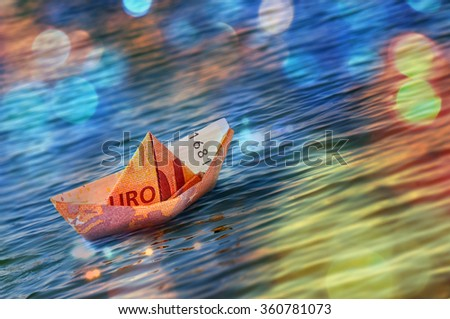 Ten euro origami boat on the sea. - stock photo