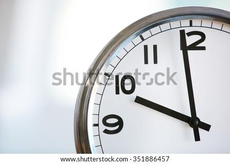 Ten o'clock on the white wall clocks - stock photo