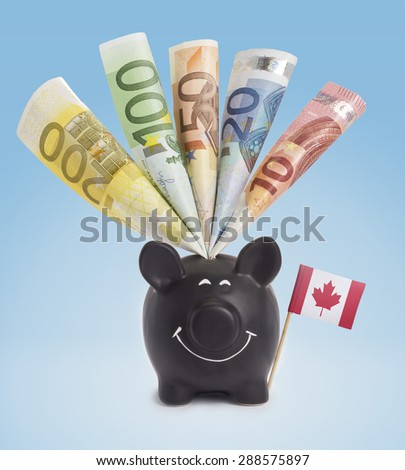 Ten,twenty,fifty,one hundred and a 200 Euro banknote in a smiling piggybank of Canada.(series) - stock photo
