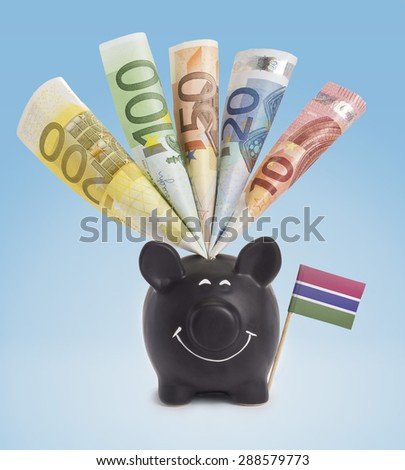 Ten,twenty,fifty,one hundred and a 200 Euro banknote in a smiling piggybank of Gambia.(series) - stock photo