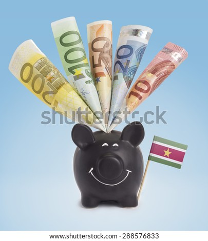 Ten,twenty,fifty,one hundred and a 200 Euro banknote in a smiling piggybank of Suriname.(series) - stock photo