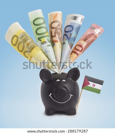 Ten,twenty,fifty,one hundred and a 200 Euro banknote in a smiling piggybank of Western Sahara.(series) - stock photo