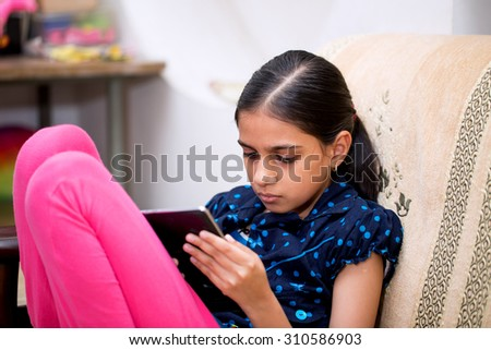 ten year girl playing with her tablet pc or tab in her house sitting on a sofa or a wooden chair against white curtain - stock photo