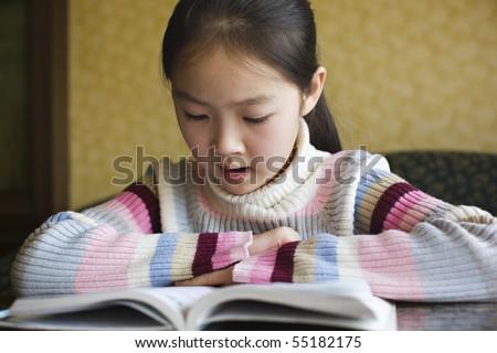ten-year old asian schoolgirl reading a book - stock photo