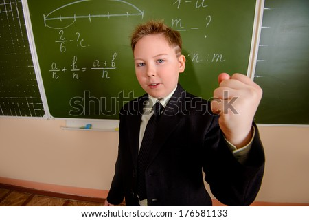 Ten years boy shakes his fist at someone at a classroom.  - stock photo