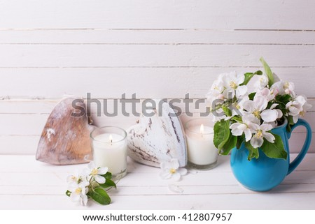 Tender apple tree flowers, hearts and candles on white wooden background. Selective focus. Place for text. - stock photo