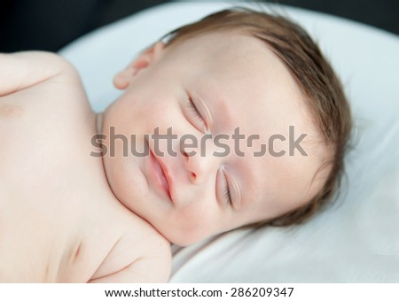 Tender baby smiling while nap in the crib - stock photo