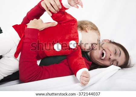 tender funny one year age caucasian blonde cute lovely baby Santa Claus Christmas disguise with brunette woman mother embraced laughing together lying on white floor background - stock photo