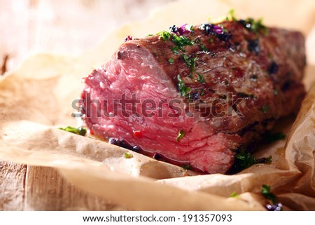 Tender lean rare roast beef seasoned with fresh herbs and spices on a piece of oven paper - stock photo