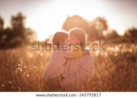tender mother with daughter on the hands in a wheat field, On the Sunset embrace - stock photo