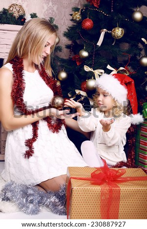 tender photo of cute little girl with blond curly hair,wearing Santa's hat and playing with her pregnant mother beside a decorated Christmas tree - stock photo