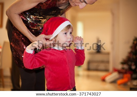 tender portrait of woman mother red dress placing hat to two years age caucasian blonde cute lovely baby Santa Claus disguise indoor with Christmas tree and gifts boxes - stock photo