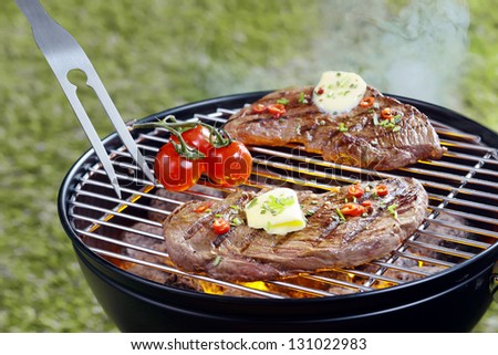 Tender steak topped with a curl of butter and herbs grilling outdoors on a portable barbecue with a pronged fork and tomatoes - stock photo