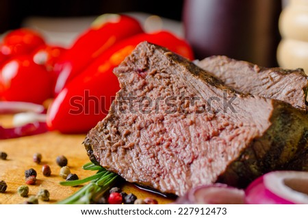 Tender succulent slice of roast beef showing the texture of the meat on a board with red peppers, peppercorns, rosemary and onion - stock photo