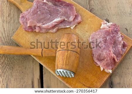 Tenderize slabs of meat on wooden board - stock photo