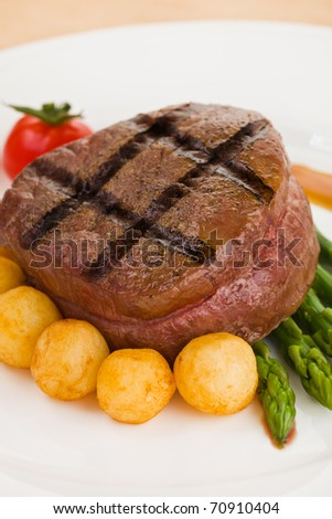 Tenderloin steak in a white plate with vegetable. Shallow depth of field. - stock photo