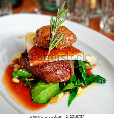 Tenderloin steak with beef terrine and spinach in plate - stock photo