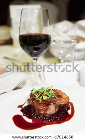 Tenderloin steak with red sauce on arranged table - stock photo
