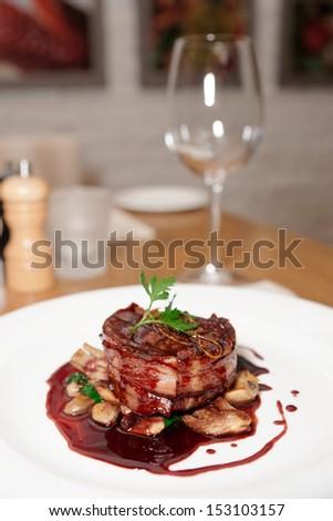 Tenderloin steak wrapped in bacon on restaurant table - stock photo