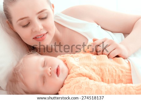 Tenderness. Mother watching her sleeping baby in bed - stock photo