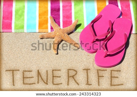 Tenerife beach travel concept background. TENERIFE written in sand with water next to beach towel, summer sandals and starfish. Summer and sun vacation holidays on Canary Islands, Spain. - stock photo