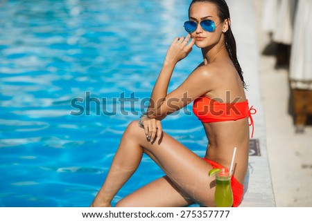 Tenned beautiful woman in orange bikini and sunlasses sitting in swimming pool with cocktail. Fashionable portrait. Elegant woman in a bikini and sunglasses - stock photo