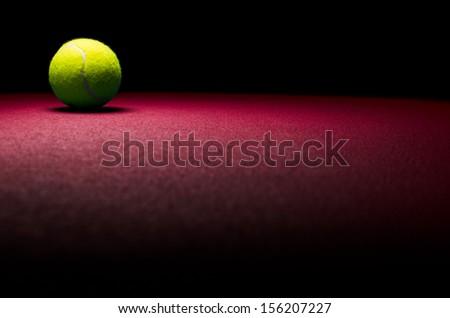 Tennis background - low key ball in corner with red surface - stock photo