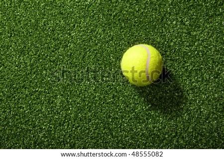 Tennis ball against fake grass texture background - stock photo