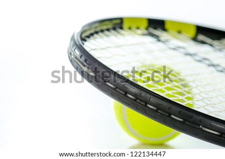 Tennis ball and racket against a white background - stock photo