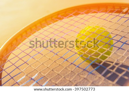 Tennis Ball and Racket. green color tennis ball on a tennis court sunset. - stock photo
