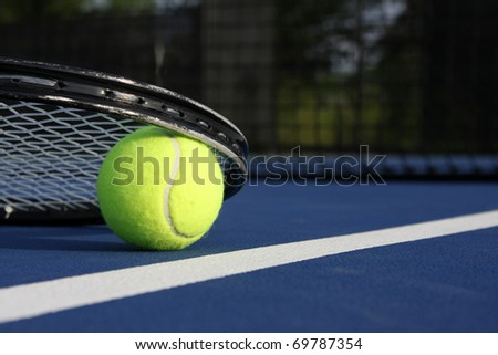 Tennis Ball and Racket on a blue court - stock photo