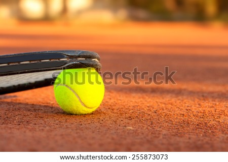 Tennis ball and racquet on a tennis clay court - stock photo