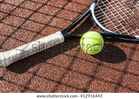 Tennis ball and tennis racket laying on court, focus on the ball - stock photo