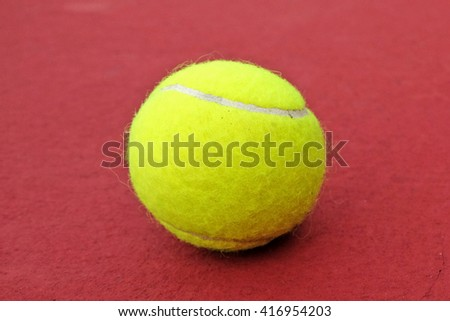 tennis ball at red background court - stock photo