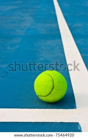 Tennis ball beside white line - stock photo