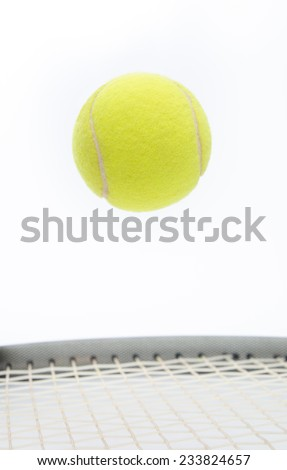 Tennis ball jumping and levitating over a racket suggesting the a stop motion on a game point - stock photo