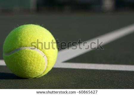 Tennis Ball near the center court lines - stock photo