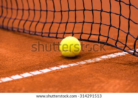 tennis ball on a clay court, close to the net - stock photo