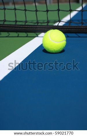 Tennis ball on blue court at the net - stock photo