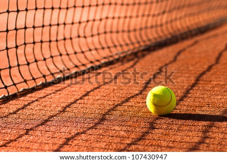 tennis ball on court just behind the net - stock photo