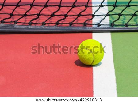 Tennis ball on green tennis court - stock photo