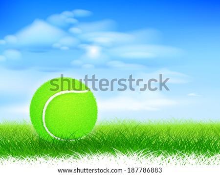 Tennis ball on lush grassy field. - stock photo