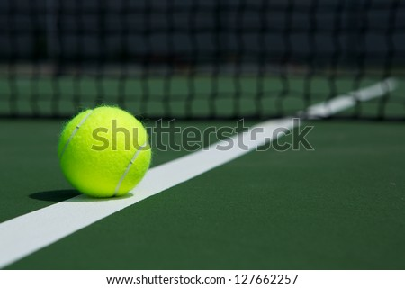 Tennis Ball on the Court Close up with Net in the Background - stock photo