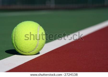 Tennis ball on the court line diagonal - stock photo