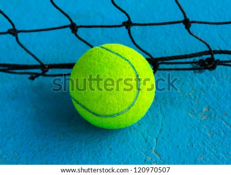 Tennis ball on the court with the net background - stock photo